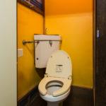 洋式トイレです。壁は明るい黄色です。